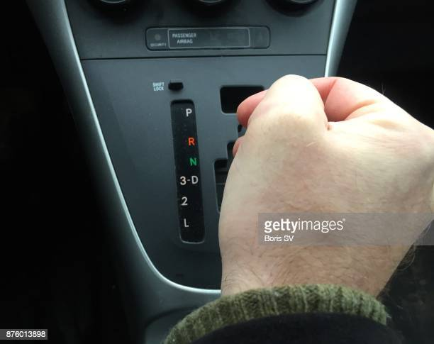 Man switching gear of automatic transmission, on the road