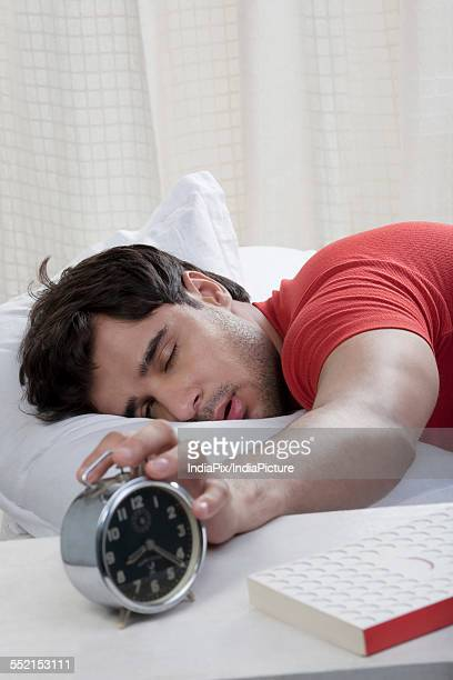 Man switching off his alarm clock