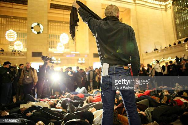 A man symbolically chokes himself with a scarf during a protest in Grand Central Terminal December 3 2014 in New York Protests began after a Grand...
