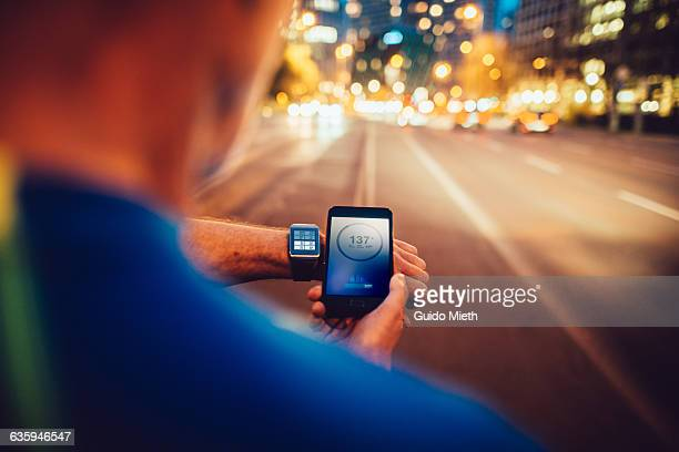 Man synchronising smartwatch and mobile phone.
