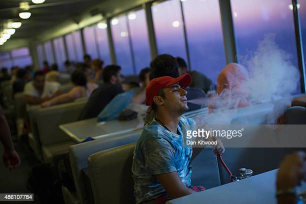 A man Syrian man smokes Sheesha on the Blue Star ferry bound for Athens from Kos on August 31 Greece Migrants from many parts of the Middle East and...