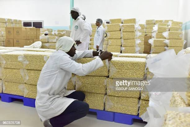 Man tags bags of processed cashew nuts in a factory in the central Ivorian city of Bouake on May 24, 2018.