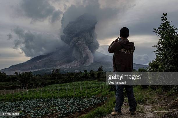 A man take a picture as Mount Sinabung spews pyroclastic smoke seen from Tiga Kicat village on June 20 2015 in Karo District North Sumatra Indonesia...