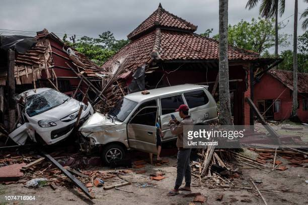 A man take a picture of damaged cars and buildings after being hit by tsunami at a hotel resort on December 24 2018 in Carita Banten province...