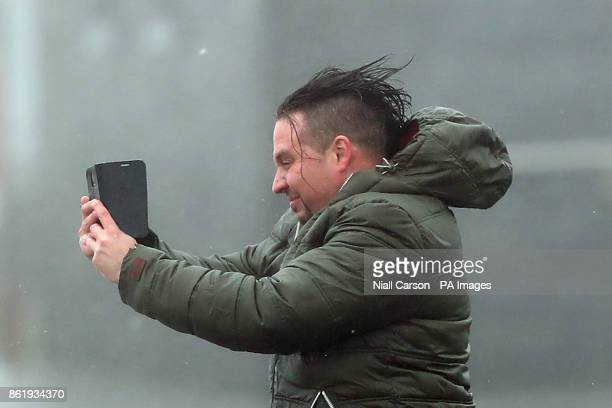 A man take selfies in waves and high wind at Lahinch in County Clare on the West Coast of Ireland as Hurricane Ophelia hits the UK and Ireland with...