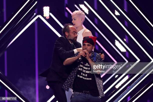 A man take the stage to interrupt singer SuRie of United Kingdom performs during the 2018 Eurovision Song Contest Grand Final at the Altice Arena in...