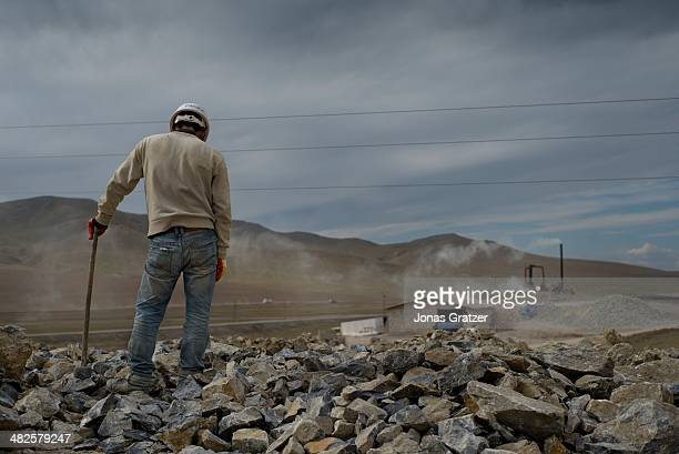 Man takes a break from mining hard rocks on the outskirts of the Sharyngol district in Mongolia where virtually everyone in the city works in the...