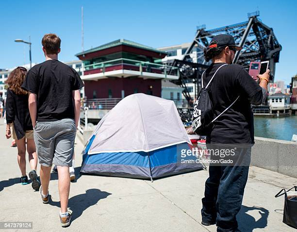 A man takes a cellphone photograph and two people walk casually past a tent which is part of a homeless encampment San Francisco California 2016