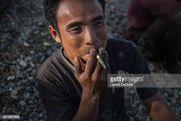 A man takes a cigarette break from recycling oil on December 16 2013 in Yangon Myanmar Large cargo ships on the Irrawaddy River in Myanmar have oil...