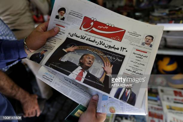 A man takes a glance at a newspaper with a picture of US president Donald Trump on the front page in the capital Tehran on July 31 2018 Iran's...