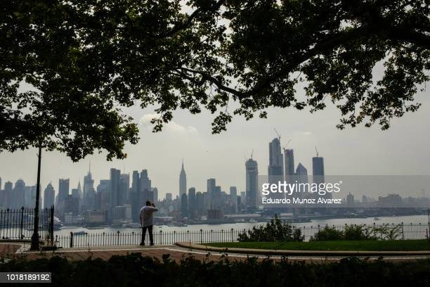A man takes a look of the haze over the New York skyline and Empire State Building on August 17 2018 in Weehawken New Jersey Severe thunderstorms and...