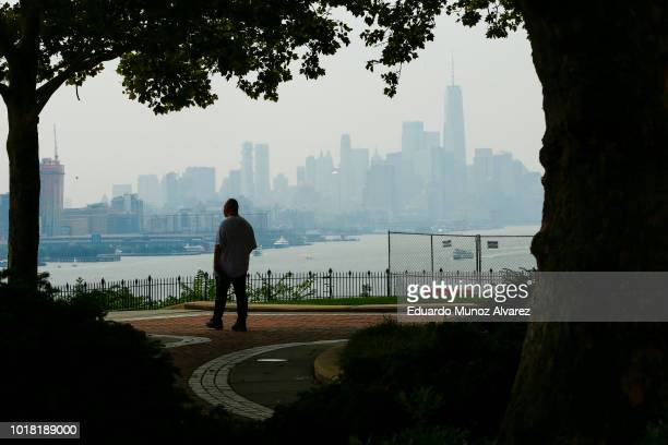 A man takes a look of the haze over the New York skyline and One World Trade Center on August 17 2018 in Weehawken New Jersey Severe thunderstorms...