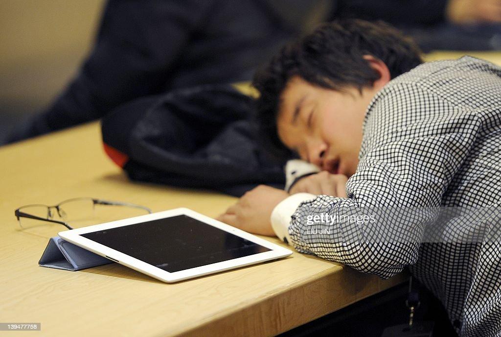 A man takes a nap next to his Ipad at a : News Photo