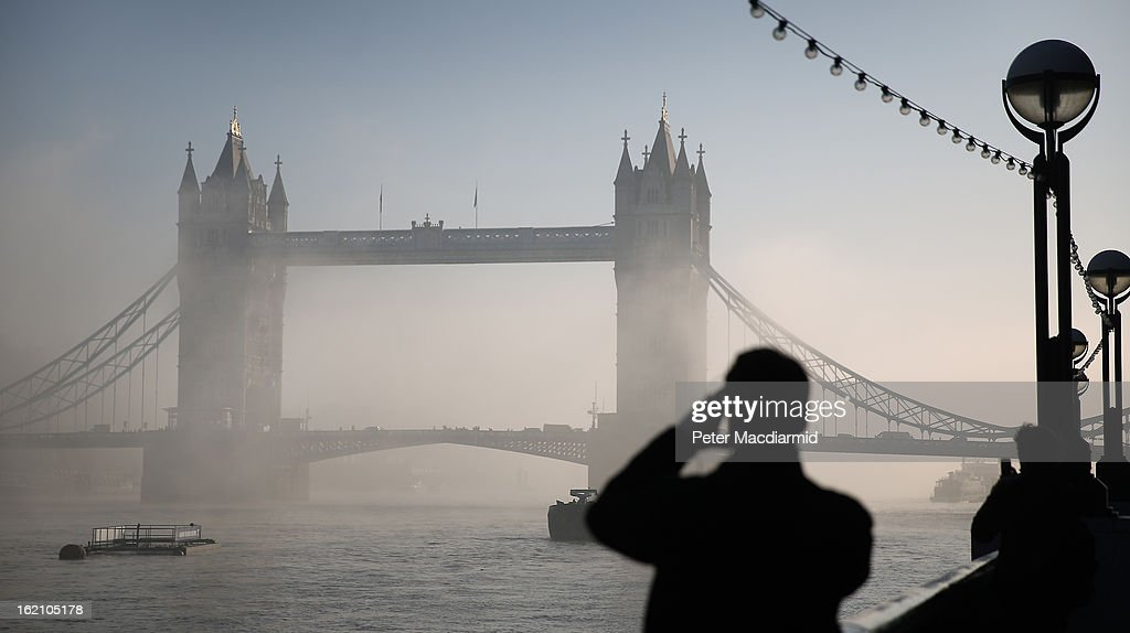 A man takes a phone photograph of Tower Bridge as it emerges from early morning fog on The River Thames on February 19, 2013 in London, England. Heathrow was forced to cancel a number of flights and London City Airport suffered distruptions as a result of poor visibility due to fog.