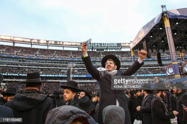 TOPSHOT A man takes a photo as people gather in MetLife Stadium on January 1 in East Rutherford New Jersey to mark the Siyum HaShas an event that...