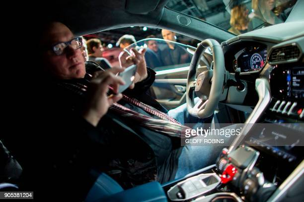 A man takes a photo in the new Lamborghini Urus during a press event alongside the 2018 North American International Auto Show Press Preview in...