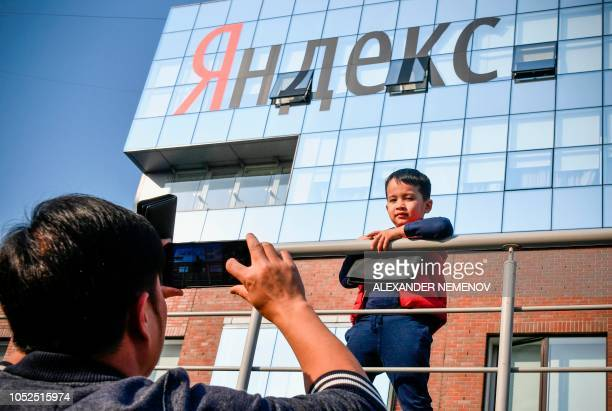 A man takes a photo of a child outside the headquarters of Yandex company Russia's internet search engine in Moscow on October 19 2018 The Russian...