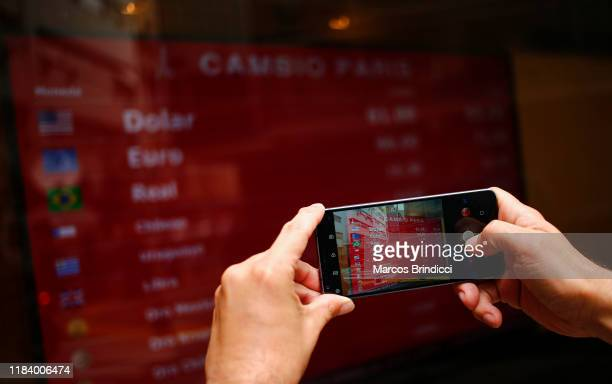 A man takes a photo of a currency exchange board on October 28 2019 in Buenos Aires Argentina National Central Bank restricted the limit for dollar...