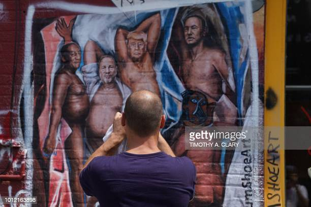 A man takes a photo of a graffiti mural in the Williamsburg section of Brooklyn New York on August 6 2018 by New Yorkbased artist Angela China with...