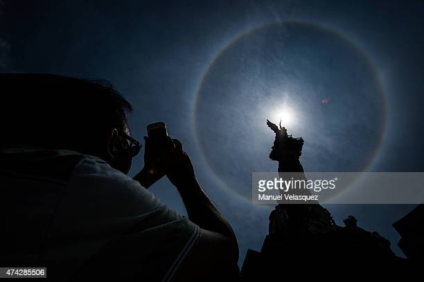 Man takes a photo of a halo around the sun at Angel de la Independencia on May 21 in Mexico City, Mexico. The halo is one type of optical phenomenon,...