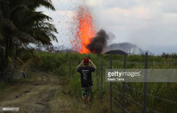 A man takes a photo of a lava fountain from a Kilauea volcano fissure on Hawaii's Big Island on May 18 2018 in Kapoho Hawaii The US Geological Survey...
