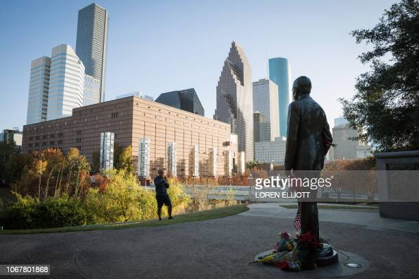 A man takes a photo of a monument of former US President George H W Bush where mourners have created a makeshift memorial in Houston Texas on...