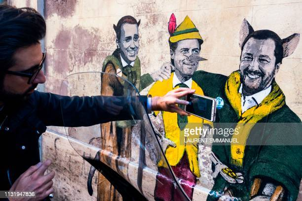 A man takes a photo of a mural by Italian street artist TvBoy entitled The cat and the fox Il gatto e la volpe showing Italys Labor and Industry...