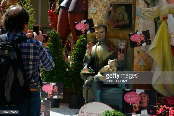 A man takes a photo of a ninot representing member of the PSOE Pedro Sanchez during the Fallas Festival in Valencia on March 16 2017 Fallas are...