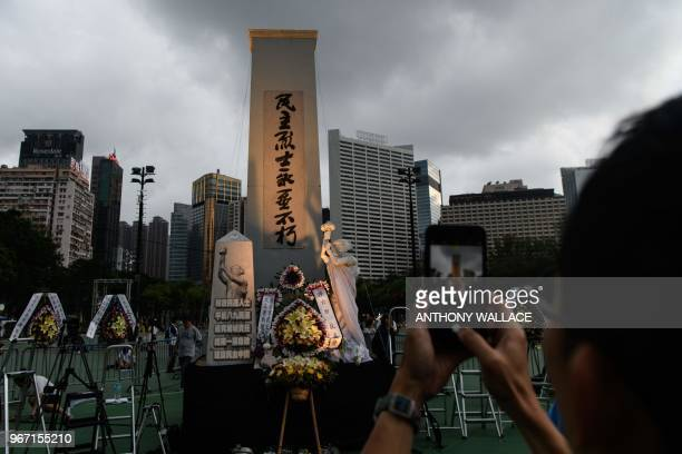A man takes a photo of a statue depicting the Goddess of Democracy ahead of a candlelight vigil in Hong Kong on June 4 2018 to mark the 29th...