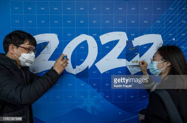 Man takes a photo of a woman as she signs a '2022' poster at an event held by the organizing committee of the Beijing 2022 Winter Olympics and...