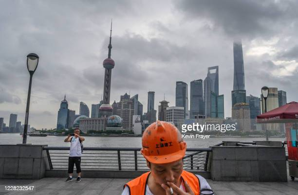 Man takes a photo of himself next to the Huangpu River as the skyline of the city is is seen, including the Oriental Pearl TV Tower and the Shanghai...