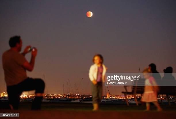 A man takes a photo of his children as the 'Blood Moon' rises over the water in Wlliamstown on April 15 2014 in Melbourne Australia The Lunar Eclipse...