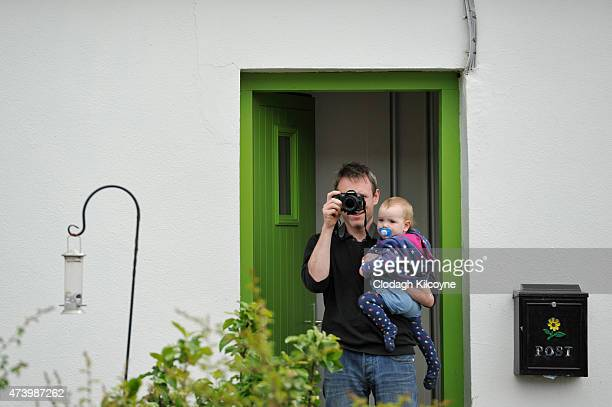 A man takes a photo of the arrival of Camilla Duchess of Cornwall to Claddagh primary school across the road from his home on May 19 2015 in Galway...
