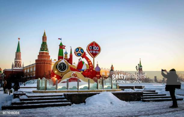 TOPSHOT A man takes a photo of the digital FIFA World Cup 2018 countdown clock placed in front of the Red Square and the Kremlin in Moscow marking...