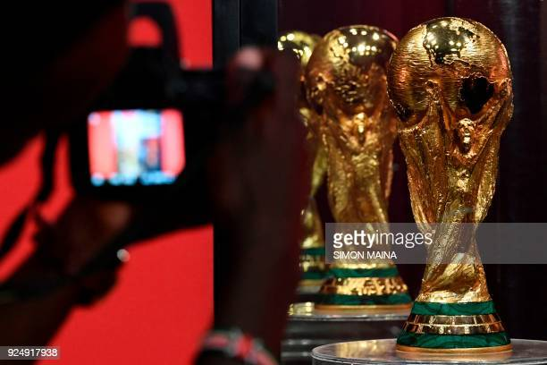 A man takes a photo of the FIFA World Cup Trophy displayed at the Kenyatta International Confernce Center in Nairobi on February 27 2018 part of the...