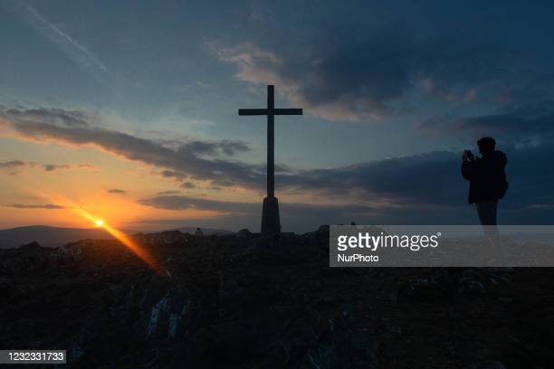 Man takes a photo of the Holy Year Cross on summit of Bray Head at sunset, during the COVID-19 lockdown. On Thursday, 15 April 2021, in Bray, County...