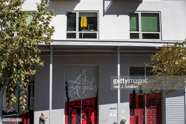 Man takes a photo of the scene as a Kobe Bryant jersey hangs in a window following the Lakers championship win on Monday, Oct. 12, 2020 in Los...