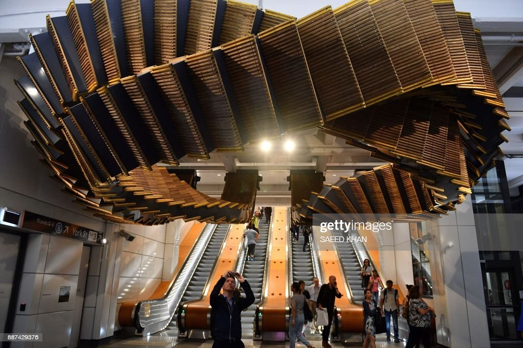 A man takes a photo of the sculpture 'Interloop', made from old wooden escalators in Wynyard railway station, by artist Chris Fox in Sydney on December 7, 2017. The decades-old wooden escalators in Wynyard station were replaced by modern escalators as part of the station's redevelopment. / AFP PHOTO / Saeed KHAN / RESTRICTED