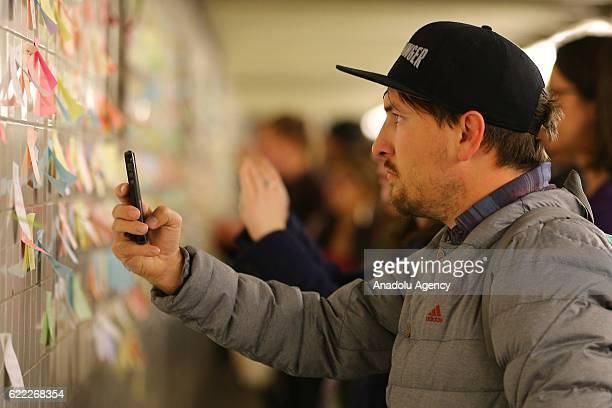 A man takes a photo of the wall as the people write their messages on selfstick paper as a part of Voice Actor Matthew Chavez's public art project...