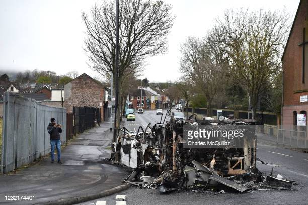 Man takes a photo on his mobile phone as he walks past a burnt down bus on April 8, 2021 in Belfast, Northern Ireland. Violence broke out after a...