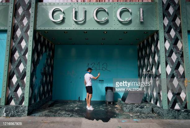 A man takes a photo outside a looted Gucci store on the iconic Rodeo Drive after demonstrators protested the death of George Floyd in Beverly Hills...
