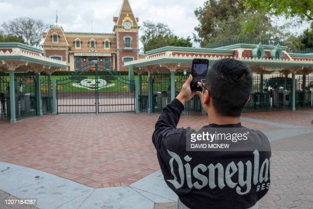 A man takes a photo outside the gates of Disneyland Park on the first day of the closure of Disneyland and Disney California Adventure theme parks as...