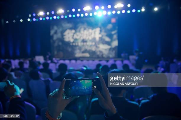 A man takes a photo with a smartphone ahead of the Xiaomi Technology new Surge S1 chipset presentation at a launch event in Beijing on February 28...