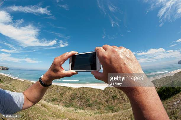 A man takes a photo with his camera phone at the beach