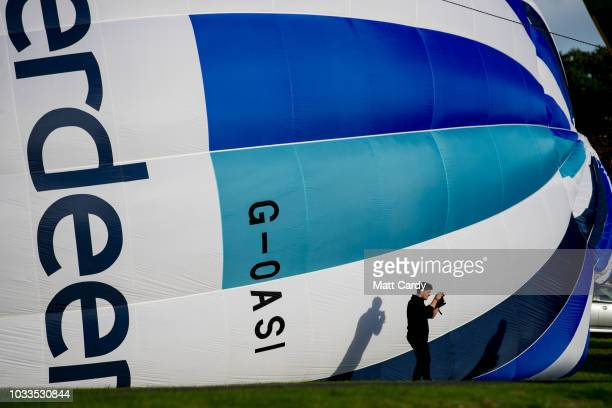 A man takes a photograph as a hot air balloon is inflated at Longleat's Sky Safari at Longleat on September 15 2018 near Warminster in Wiltshire...
