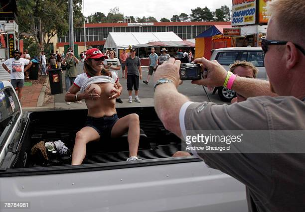 A man takes a photograph as a woman displays her breasts in the back of a vehicle during Street Machine Summernats 21 Car Festival at Epic Park on...