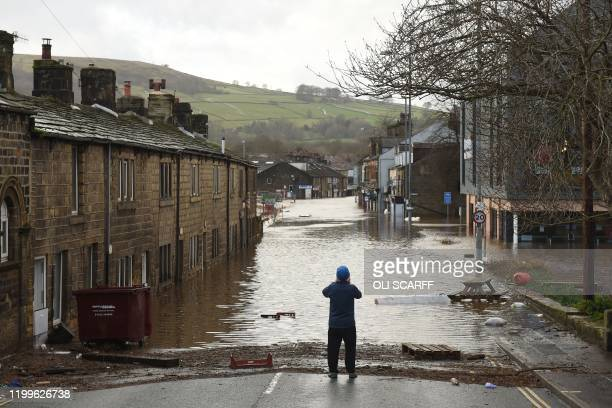A man takes a photograph as flood water covers the roads and car parks in Mytholmroyd northern England on February 9 after the River Calder burst its...