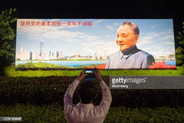 Man takes a photograph at Deng Xiaoping Portrait Square in Shenzhen, China, on Thursday, Nov. 19, 2020. XiJinping wants a stronger, more disciplined...
