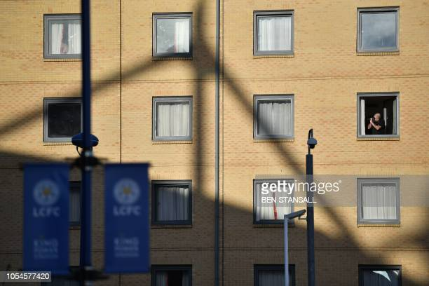 A man takes a photograph from a hotel window of Leicester City Football Club's King Power Stadium in Leicester eastern England on October 28 2018...