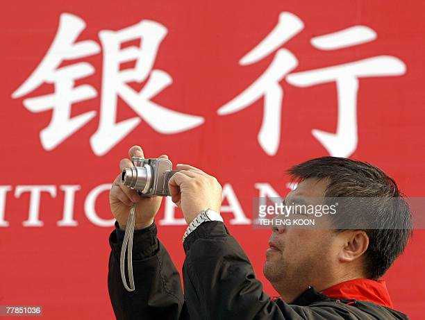 A man takes a photograph in front of a Chinese bank advertisment billboard displayed at the Beijing International Finance Expo in Beijing 11 November...